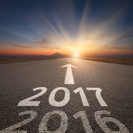 Driving on an empty road towards the setting sun and sunbeams to upcoming new 2017 year and leaving 2016 behind. Concept for success and passing time. Banco de Imagens