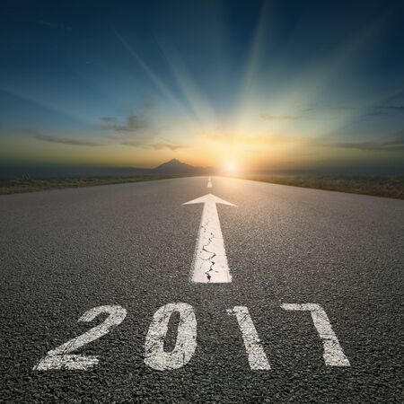 the passing of time: Driving on an empty road towards the setting sun and sunbeams to upcoming new 2017 year. Concept for success and passing time.
