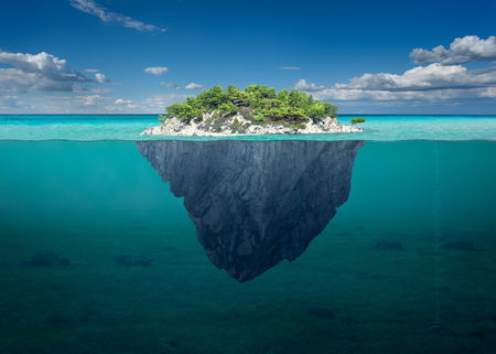 Idyllic underwater view of lone small island above and below the water surface in turquoise waters of tropical ocean. 스톡 콘텐츠