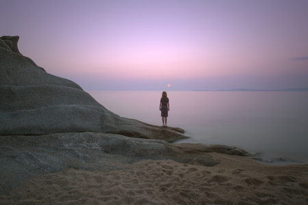 landscape: Woman standing on an edge of the shore and watching the sunrise by rocks with strange shape. Long exposure shot in Aegean Sea, Greece.