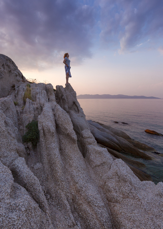 Lone woman standing on an edge of cliff and watching the setting sun from the shore with strange rocks. Coastline of Aegean Sea, Greece.