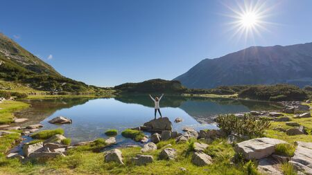 single: Single woman hiker with white shirt greeting the sun, raising his arms in the air near Muratovo lake on the mountain range of National Park Pirin, Bulgaria.