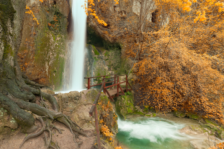 downstream: Beautiful waterfall in late autumn time with a wooden bridge as viewpoint and tree roots in the foreground.