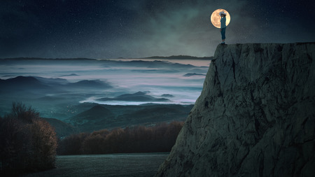 Lonely woman standing on the edge of a cliff on the night of the full moon with a view of valley covered with fog. Stock Photo
