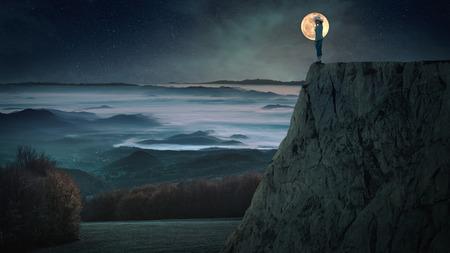 noche y luna: Mujer sola que se coloca en el borde de un acantilado en la noche de la luna llena con una vista del valle cubierto de niebla.