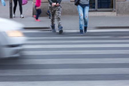 paso de peatones: calle de la ciudad llena de gente y coche en el desenfoque de movimiento de cruce de peatones. escena peligrosa sin tener en cuenta las normas de tráfico. concepto de velocidad.