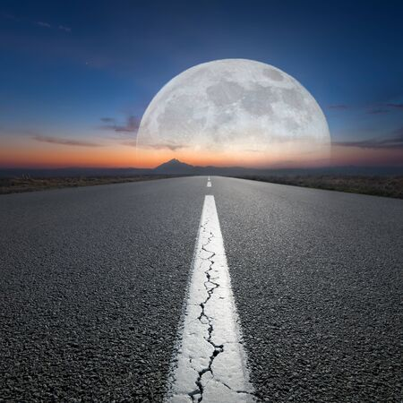 moon  desert: Empty highway leading to the mountains through the desert against the rising big full moon at night. Success concept.
