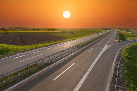 Empty, straight highway towards the sun at beautiful spring sunset near Belgeade, Serbia.