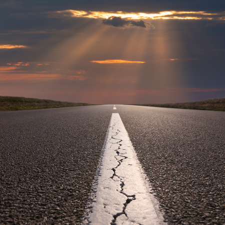 cracked: Empty highway leading to the beautiful clouds and sunbeams, against the setting sun at idyllic sunset. Success concept.