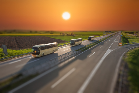 Modern golden buses driving in blurred motion on the freeway at beautiful sunset in tilt shift technique. Transport and travel scene on the motorway near Belgrade, Serbia.