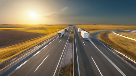 Delivery trucks driving towards the sun. Fast blurred motion image on the freeway in beautiful autumn scenery. Freight scene on the motorway near Belgrade, Serbia.