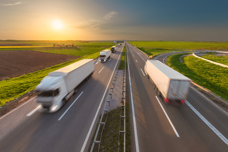 Many delivery trucks driving through agricultural fields. Fast blurred motion image on the freeway at beautiful sunset. Freight scene on the motorway near Belgrade, Serbia. Stock Photo