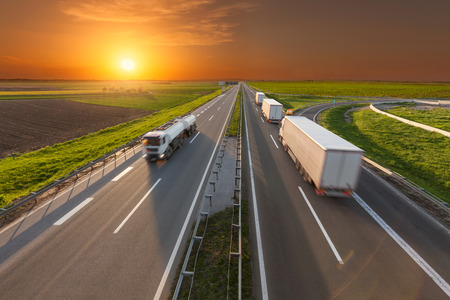 Many white trucks towards the sun. Transportation scene on the highway at beautiful sunset. Freight fast delivery on the motorway near Belgrade, Serbia.