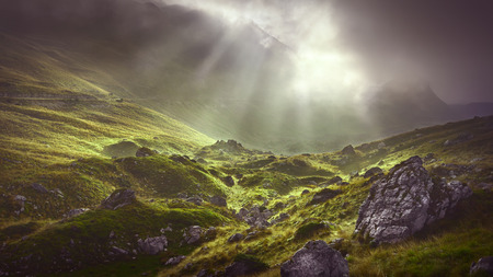 Unpredictable weather conditions in the beauty of wild mountainous terrain with sunbeams in the background.