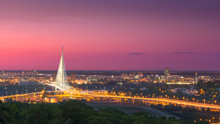 View on the New Belgrade in background, Ada Bridge landmark, as well as its access roads at idyllic purple sunset.