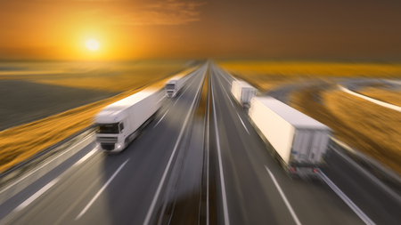 Temperature controlled reefer trucks driving towards the sun. Fast blurred motion image on the freeway at beautiful sunset. Freight scene on the motorway near Belgrade, Serbia. Stock Photo