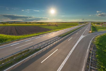 Empty, straight highway towards the sun at beautiful sunny day near Belgeade, Serbia. Stock Photo