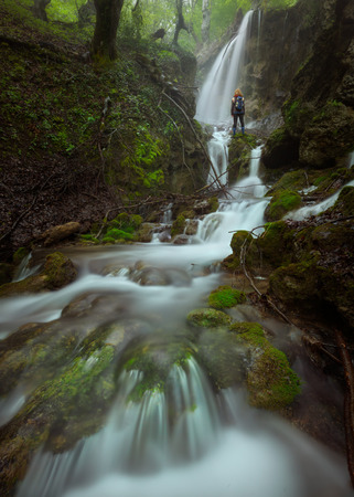 downstream: Beautiful waterfalls in woods at fogy morning and solitude woman standing next to cascades. Popular travel destination Sopotnica, Serbia.