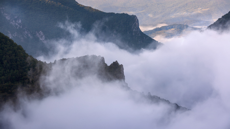 unpredictable: Mystical scene on the mountain region with dramatic movement of clouds in the valley at beautiful morning with fresh atmosphere. Canyon of the river Lim, Serbia. Stock Photo