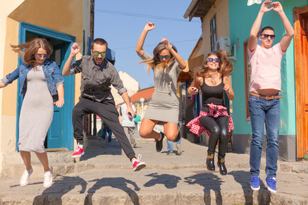 beautiful boys: Group of smiling friends jumping on the city street. Three beautiful young girls and two boys celebrating  summer in the old part of town at beautiful sunny day. Valjevo, Serbia.