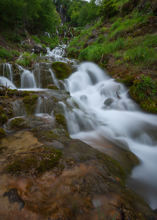 downstream: Beautiful waterfalls and cascades in woods at cloudy morning. Travel destination Sopotnica, Serbia.