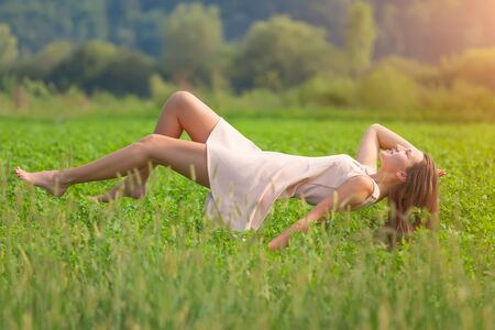 levitating: Beautiful girl in a field of clover enjoying in levitation at idyllic sunny day. Stock Photo