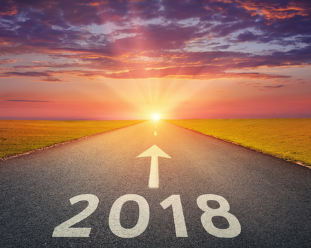 Driving on open road towards the setting sun to new year 2018. Concept for success and passing time.