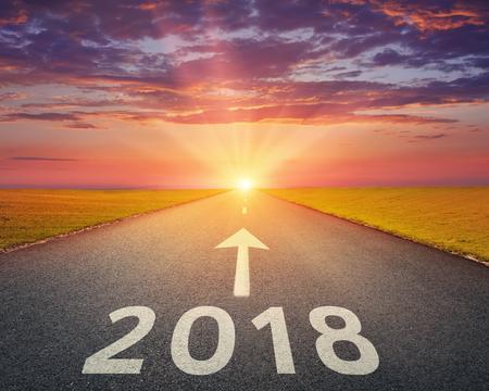 Rijden op een open weg richting de ondergaande zon tot het nieuwe jaar 2018. Concept voor succes en passerende tijd. Stockfoto
