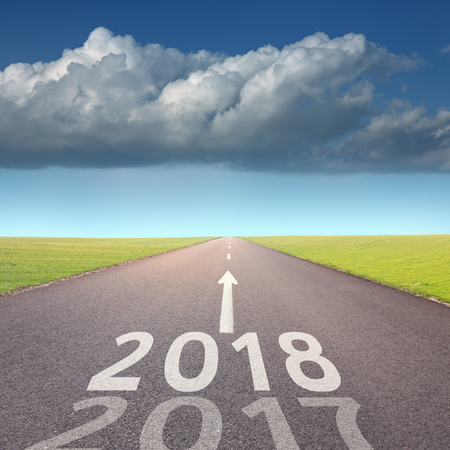 Driving on open road towards the heavy cloud to new year 2018 and leaving behind 2017. Concept for success and passing time. Banco de Imagens