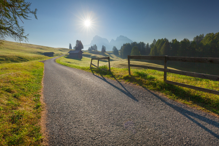 Driving on idyllic mountain road at beautiful morning. Landscape on Alpe di Siusi or Seiser Alm at Dolomites, Italy. Stock Photo