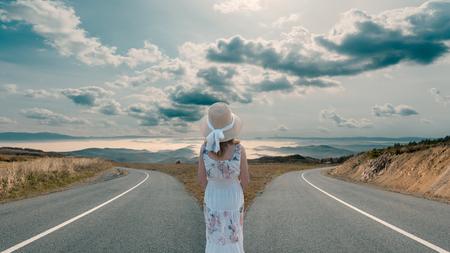 Vrouw die voor twee wegen staat en voor beste oplossing voor haar het levensreis beslist. Succes concept.