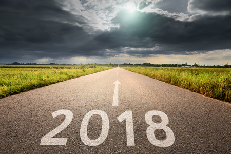 Driving forward on open road towards the big cloud to 2018 new year. Concept for future and passing time.