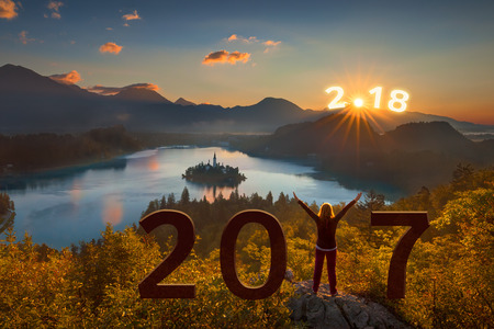 Young woman standing on summit and watching the rising sun, happy for 2018 new year and good bye 2017. Future and time passing concept.