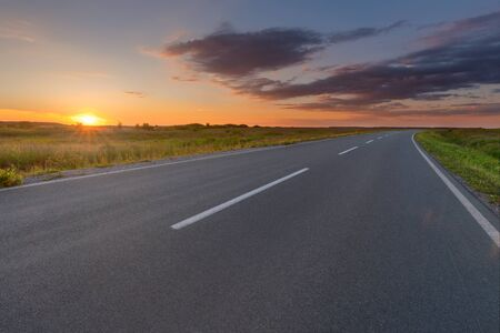 curve road: Driving on empty open road through the fields towards the idyllic sky. Freedom concept. Stock Photo