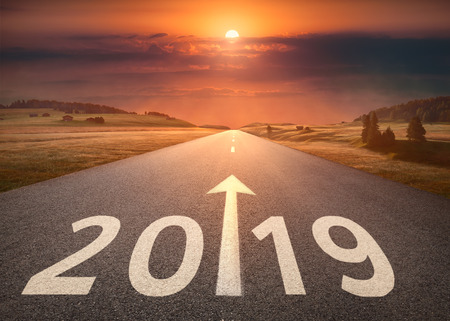 Driving on idyllic open road against the setting sun forward to new year 2019. Concept for success and future. Stock Photo
