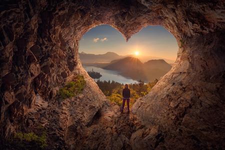 Mujer solitaria disfrutando de la hermosa naturaleza de la montaña, celebrando la libertad y de pie en el borde del acantilado contra el sol naciente. Concepto de día de San Valentín.