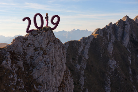 Solitude woman standing on edge of mountain ridge and contemplating beautiful landscape at sunset, uncertainty for upcoming 2019 new year. Future and time passing concept. Stock Photo