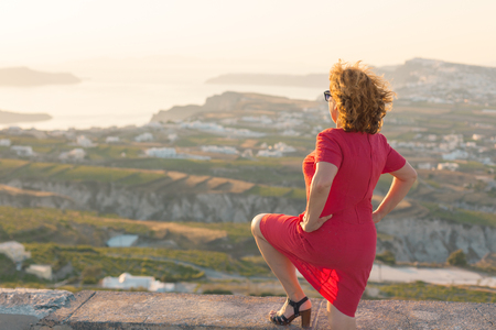 Woman contemplating with wind in the hair next to the viepoint at beautiful sunset. Lifestyle and travel concept. Santorini, Greece. Stock Photo