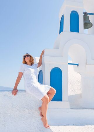 Happy barefooted woman smiling and posing next to the traditional church bell at sunny day. Lifestyle and travel concept. Santorini, Greece.