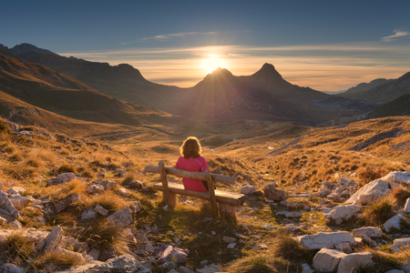 Lone woman sitting on the wooden bench and watching beautiful mountain scenery at idyllic sunrise. Durmitor National Park, Montenegro. Lifestyle and travel concept.