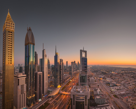 Sunset view on skyscrapers of Dubai downtown and Sheikh Zayed Road with highest hotel in the world at left end.