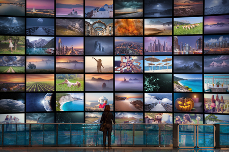 Big video wall in television production room as technology concept with colorful screens and human sihouette in front of it.