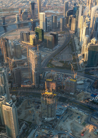 Aerial view of construction site, skyscrapers and modern technology of fastest growing city of Dubai at sunrise.
