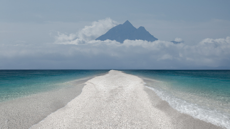 Long narrow beach next to the turquoise sea towards the high mountain peaks in the clouds. Freedom concept. Stock fotó