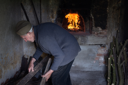 An elderly man collects wood for the cooking for baking oven as a preparation for the roasting of meat.