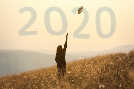 Happy woman celebrating in freedom and throwing her hat to upcoming 2020 year