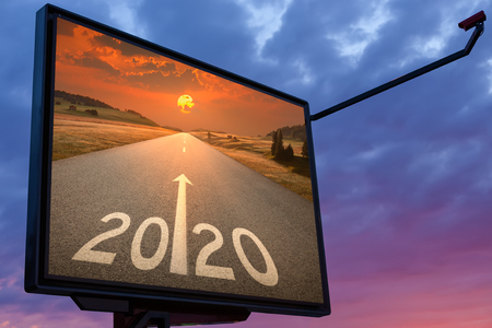 2020 on billboard with idyllic open road against the setting sun forward to better future. Concept for success.