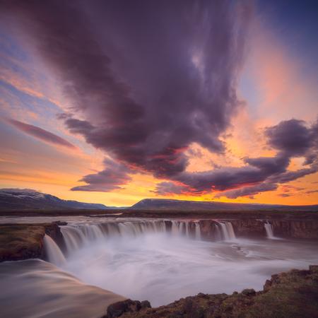 Iceland landscape photo of waterfall at idyllic sunset.
