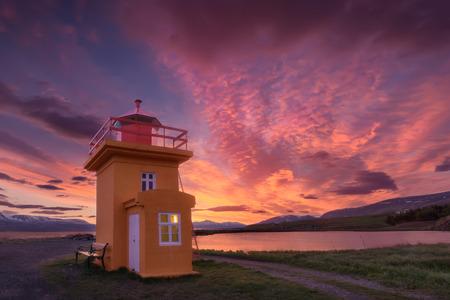 Iceland landscape photo of small orange lighthouse at beautiful sunset.