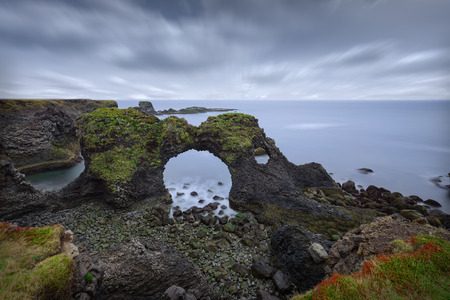 Iceland landscape scene of famous Arnastapi arch rock and cliffs at cloudy morning as long exposure photo.
